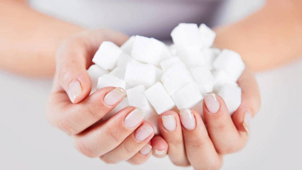 Primer plano de manos sosteniendo varios cubos de azúcar.