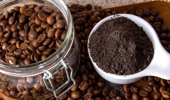 frasco de vidrio con semillas de café al lado de pequeño recipiente con café molido.