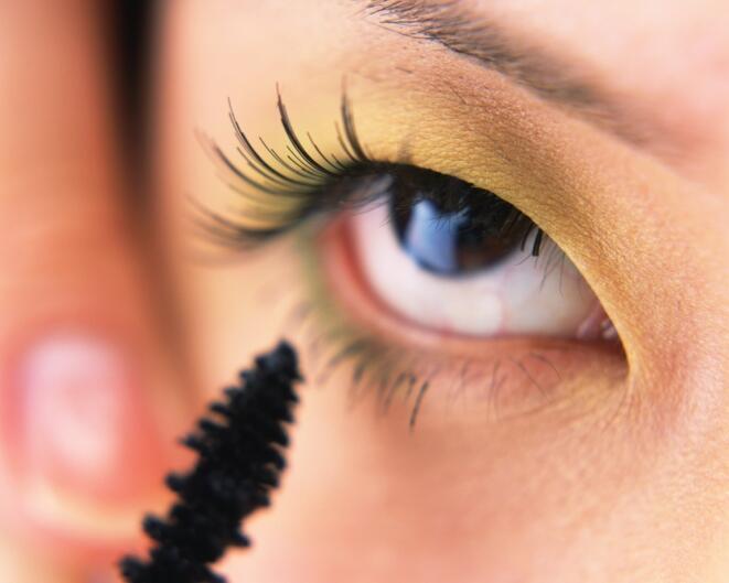 Ojo de mujer maquillando ceja postiza de esquina