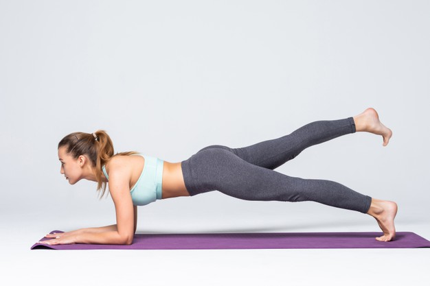 Chica que levanta la pierna mientras esta en posición de plank