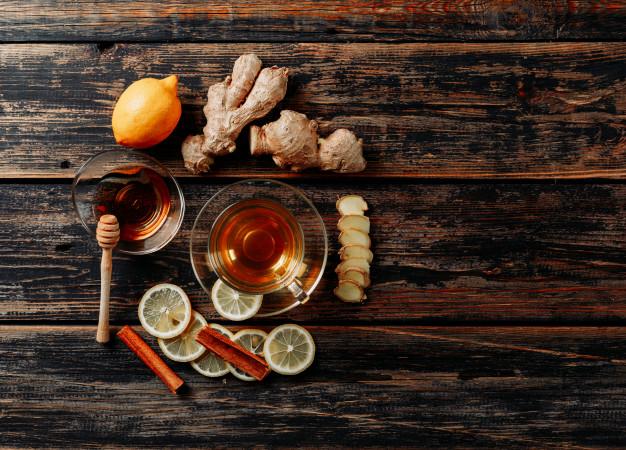 taza de té sobre una mesa con rodajas de limón, ramas de canela trozos de jengibre