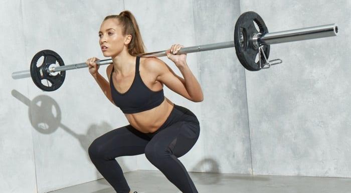 Mujer realizando ejercicio de sentadillas con barra