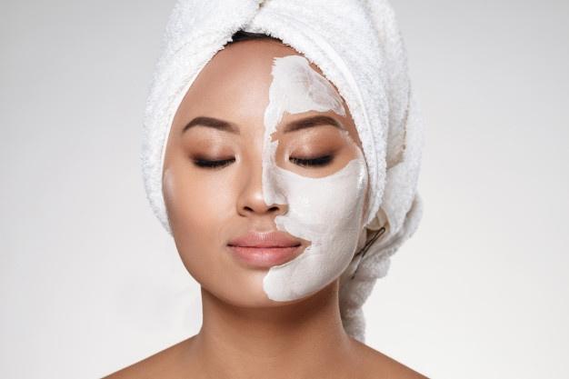 Mujer con crema antiarrugas en la mitad de la cara