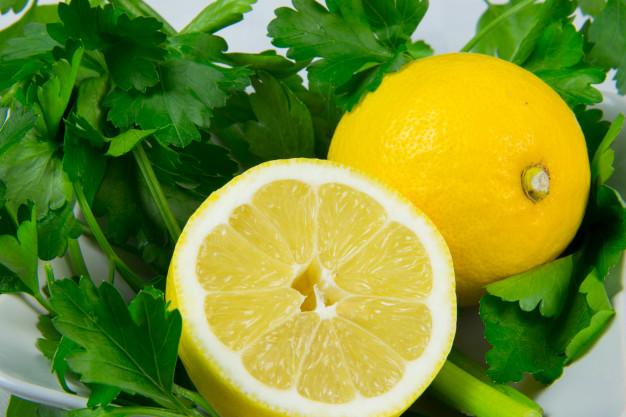 Primer plano de limón cortado a la mitad y ramas de perejil.