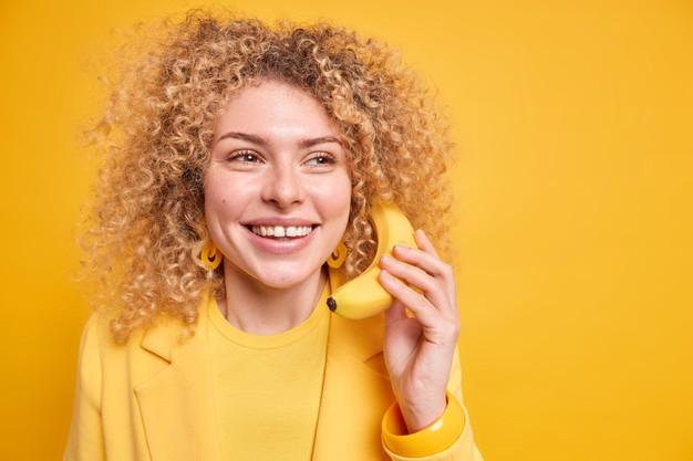 chica con cabello rizado que usa plátano en el tratamiento del cabello