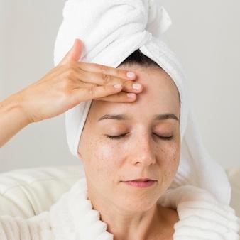 Primer plano de mujer con toalla en la cabeza colocándose crema antiarrugas en la frente