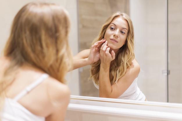 Mujer rubia tiene problemas con la piel de la cara