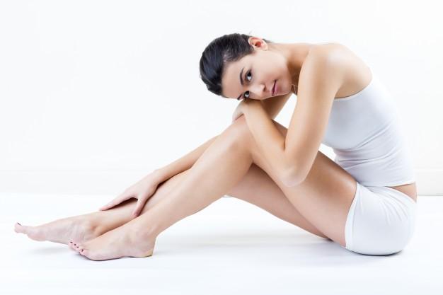 mujer sentada tocándose las piernas