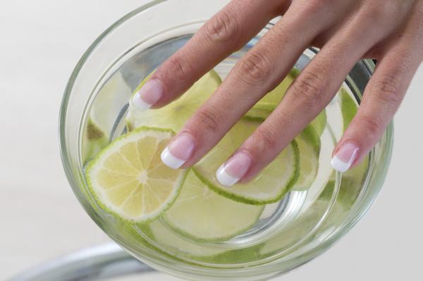 manos de mujer encima de un bol con agua y limon
