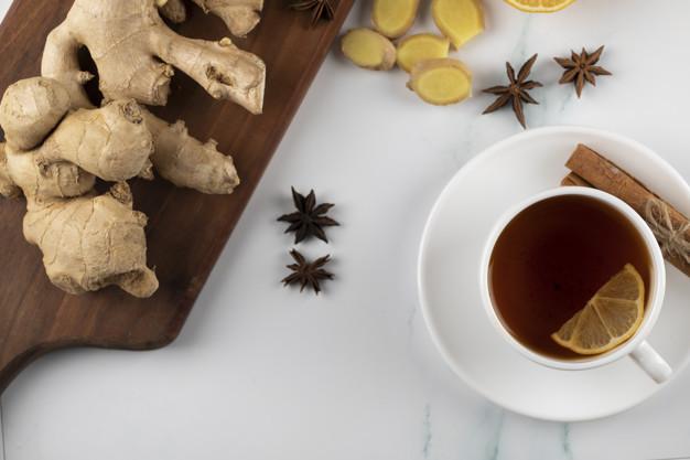 Taza de té con rama de canela y un trozo de limón, cerca de una tabla con una raiz de jengibre.