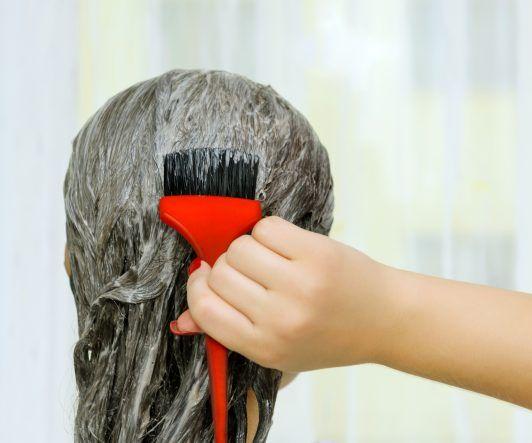 Primer plano de mujer colocandose tinte en el cabello